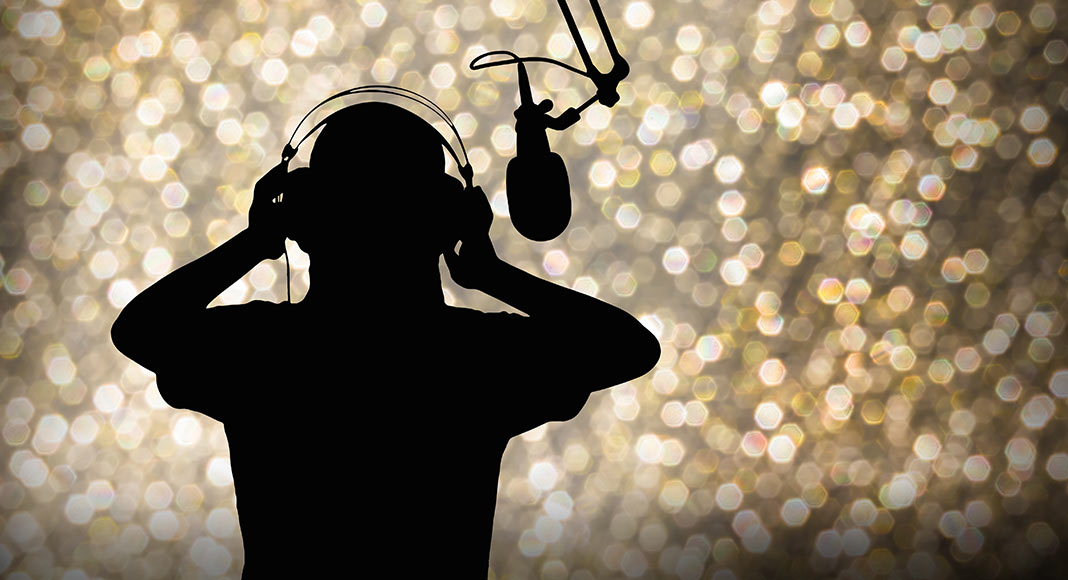 silouette of person recording into a microphone